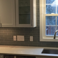 Installed tile backsplash with contrasting white grout in kitchen.