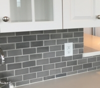 Gray ceramic subway style tile kitchen backsplash installed with contrasting white grout.